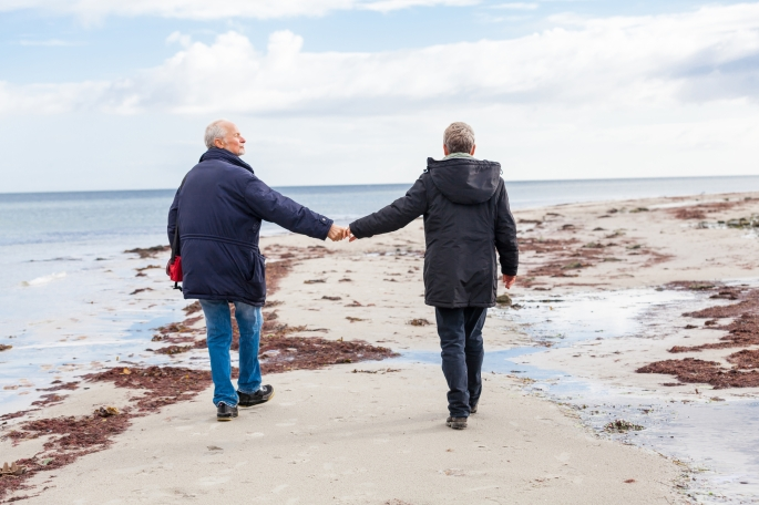 happy elderly senior couple walking on beach healthcare recreation