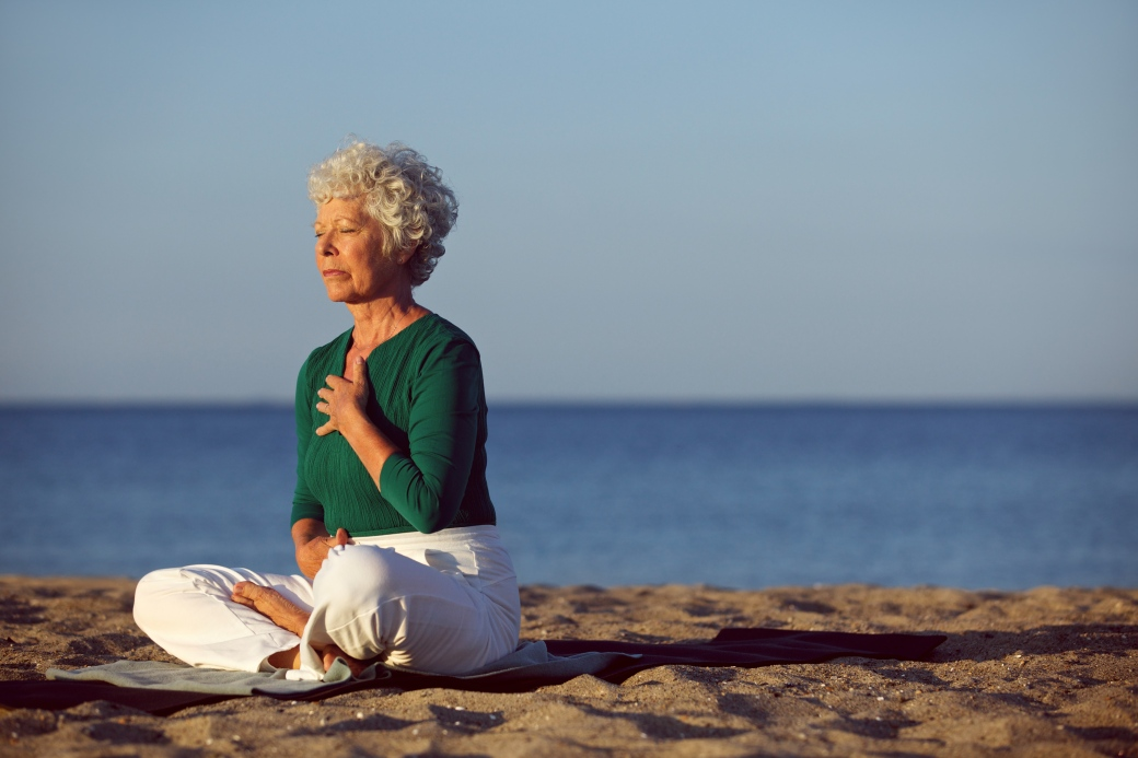 Senior woman in meditation by ocean